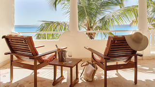 Two deck-chairs facing overlooking palm trees and the Caribbean sea
