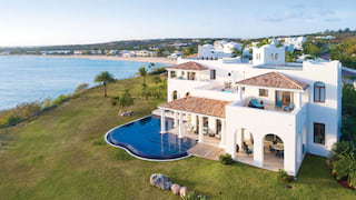 Aerial view of a large private villa and pool overlooking Baie Longue