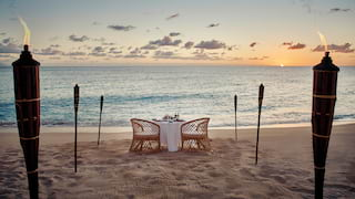Private beach table at sunset with fire-lit torches framing a sea view