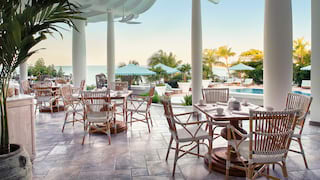 Dining tables on an outdoor terrace overlooking a pool and palm gardens
