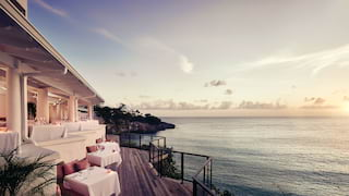 Clifftop restaurant terrace overlooking the Caribbean sea at sunset