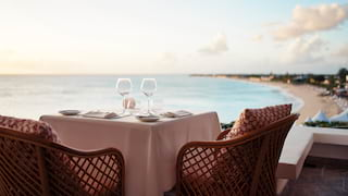 Close-up of a table for two on a terrace overlooking Baie Longue at sunset