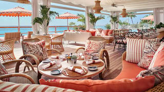 Large shaded dining terrace with informal sofa seating in vibrant coral hues