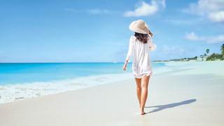 Woman walking along Baie Longue shore under sunny blue skies