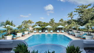 Luxury outdoor pool surrounded by sun beds and parasols under blue skies