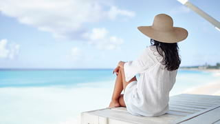 Woman wearing a sun hat and looking out to sea from a shaded beach cabana