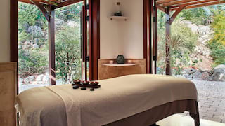 Spa treatment room with two large windows and garden views