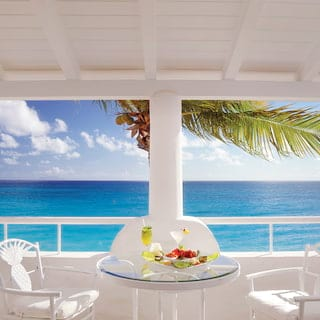 Balcony breakfast table under blue sky with Caribbean sea views