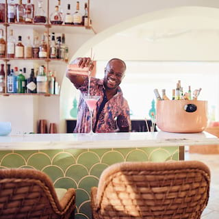 Smiling barman pouring a pink cocktail on a marble bar counter