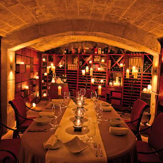 Candle-lit barrel vaulted restaurant room, with table set for private parties