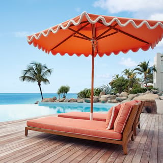 Two coral-coloured sun beds and parasol overlooking an infinity pool and blue skies