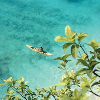 Aerial view of a lone kayaker in crystal clear waters