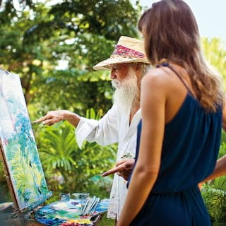 Woman in navy dress and Sir Roland Richardson painting on a canvas in tropical gardens