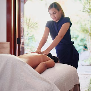 Spa therapist providing massage treatment to guest