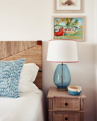 Blue cushion, bedside lamp and coin tray room details