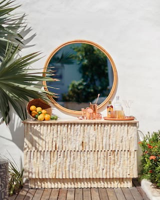 Circular mirror and palm foliage above an outdoor cocktail bar
