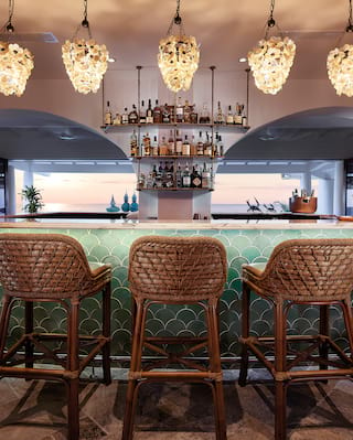 Five rattan bar stools in front of a turquoise tiled bar counter