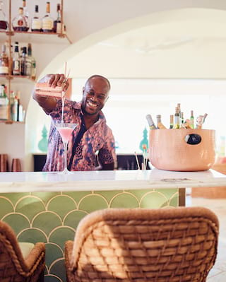 Smiling barman pouring a pink cocktail into a martini glass