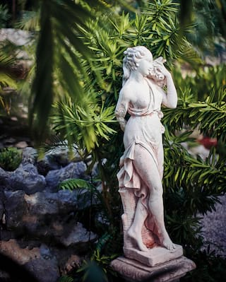 Grecian-style stone statuette among tropical gardens