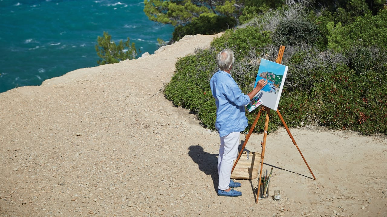 Man painting a canvas on an easel on the beach beside the blue sea