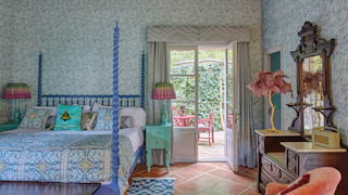 Hotel suite with vibrant wallpaper and furnishings and a terracotta-tiled floor