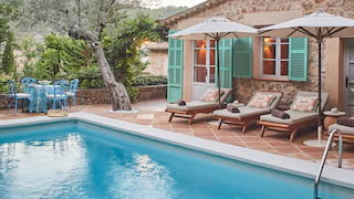 Outdoor private pool surrounded by terracotta tiles dotted with sunbeds and parasols
