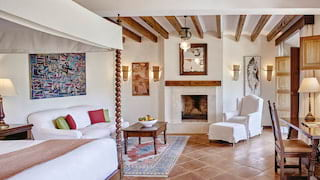Hotel suite with white furnishings, rustic fireplace and wood-beamed ceiling