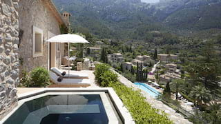 Outdoor hotel suite plunge pool next to a patio with sunbeds and parasols