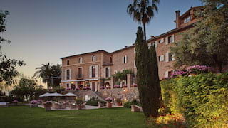 Vast stone-built Spanish villa surrounded by manicured lawns and gardens at sunset