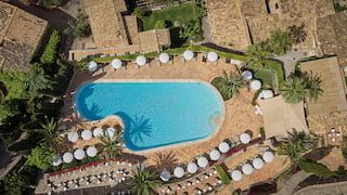 Birds-eye-view of an outdoor pool surrounded by sunbeds, parasols and palm trees