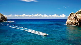 Motor boat speeding along a coastline over clear blue waters on the Mallorcan coast