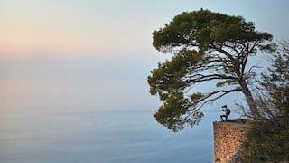 Long shot of a photographer on a Mallorcan cliffside at dawn