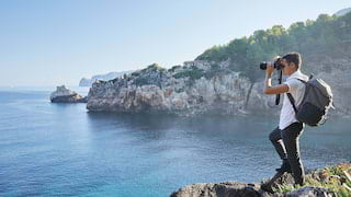 Photographer with a camera standing on a cliffside with views of sunrise over the sea