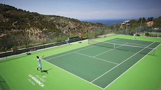 Two tennis players rallying on a large outdoor tennis court