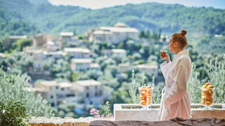 Lady in a spa robe drinking a tea while gazing across the valley village of Deia