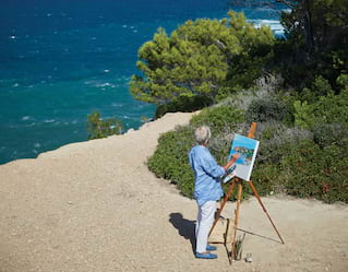 Man painting a canvas on an easel on the beach beside a blue ocean