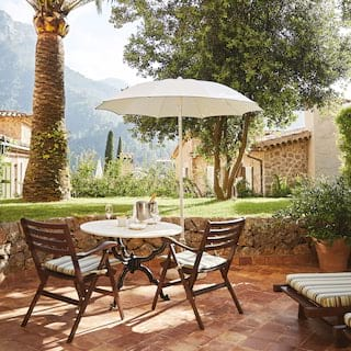 Hotel room patio with terracotta tiles, breakfast table and chairs and two sunbeds