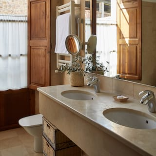 His and hers sinks below a large mirror in a bathroom with wooden window shutters