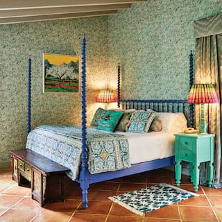 Indigo blue four-poster king-bed in a hotel room with vibrant floral wallpaper