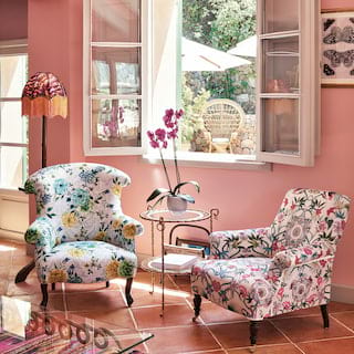 Close-up of two vibrant floral-patterned armchairs in a baby pink room