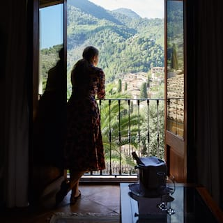 Silhouette of a lady standing at a juliette balcony overlooking a mountain valley