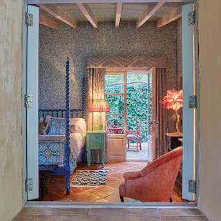 View through open window shutters of a lamplit hotel suite with vibrant furnishings