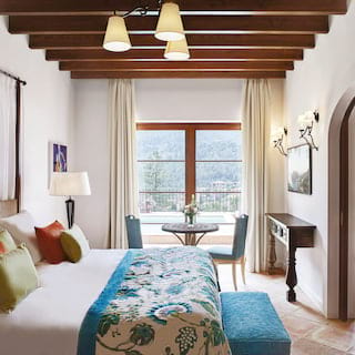 Hotel suite with a wood-beamed ceiling and plush king-bed with blue-patterned throw