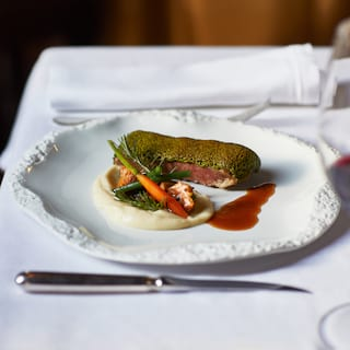 Close-up of a steak dish served with vegetables on an ornate white plate