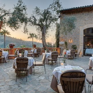 Stone-tiled restaurant patio dotted with formal candlelit tables at sunset