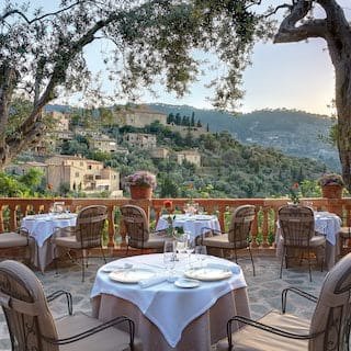 Table for two on a stone paved restaurant terrace overlooking Mallorcan mountains