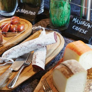 Close-up of chorizo sausages and cheeses on wooden platters at a breakfast buffet