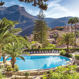 Outdoor hotel pool surrounded by palm trees overlooking the Tramuntana mountains