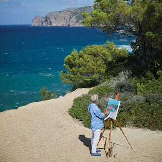 Man standing on a sandy beach painting a canvas on an easel