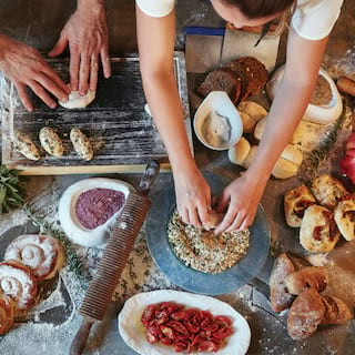 Hands kneading dough on a kitchen counter topped with various pastries